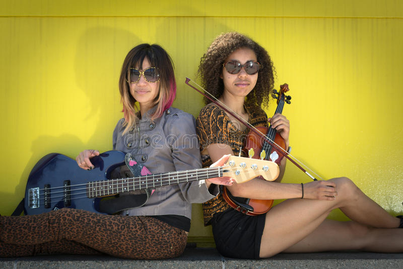 Músicos das mulheres assentados de volta à parte traseira que guarda instrumentos imagem de stock royalty free