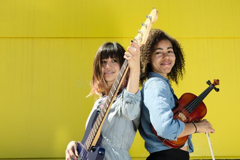 Músicos das mulheres que estão de volta à parte traseira com instrumentos imagens de stock royalty free