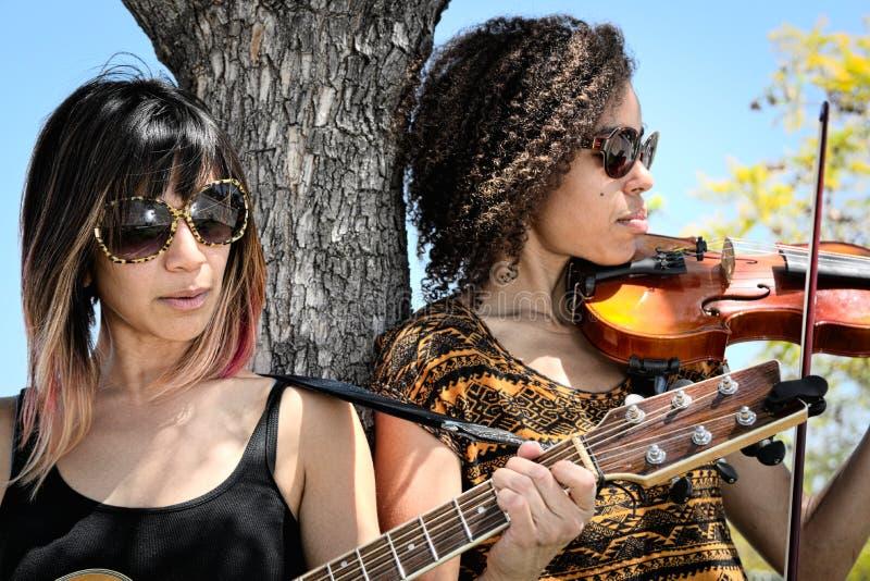 Músicos das mulheres que jogam a guitarra e o violino fora imagem de stock royalty free