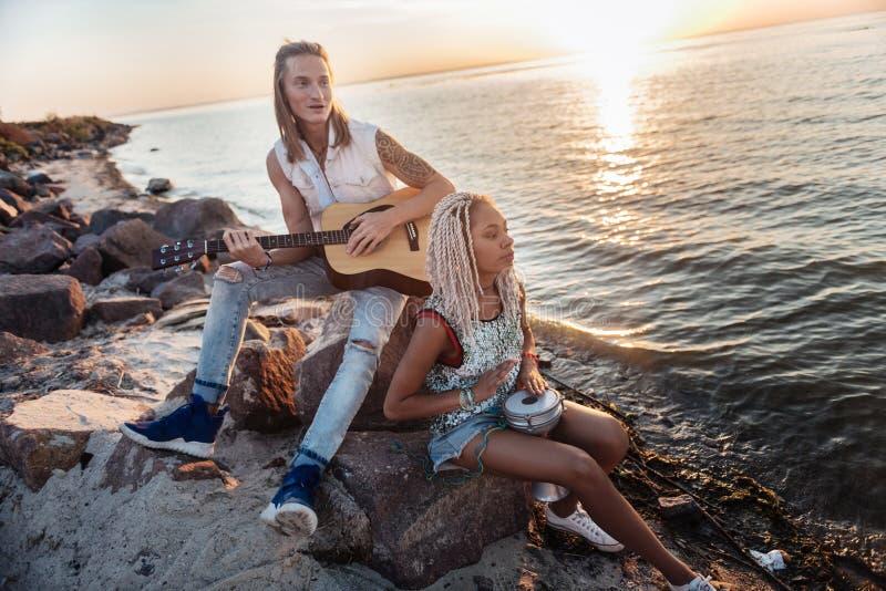 Músicos inspirados que se sientan en rocas cerca del mar y que juegan melodía preferida imagen de archivo