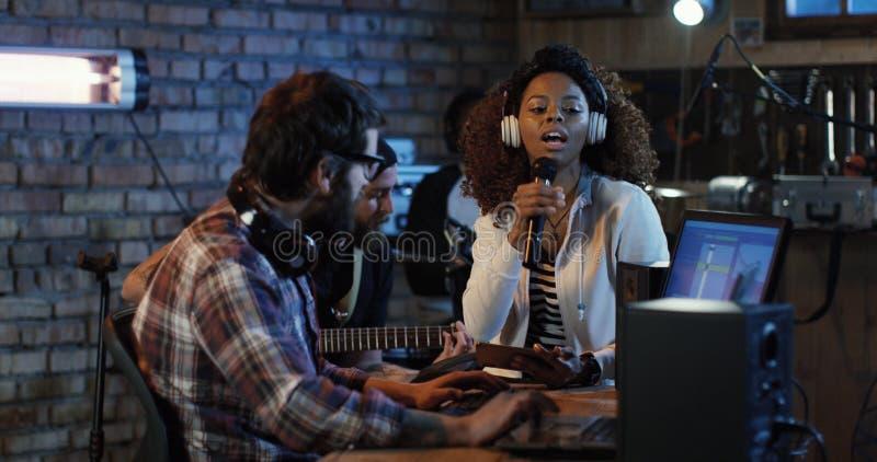 Músicos jovenes que juegan en el estudio casero fotografía de archivo libre de regalías