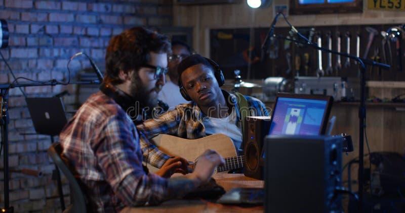Músicos jovenes que juegan en el estudio casero imagen de archivo
