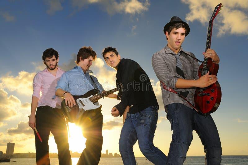 Músicos masculinos novos com os instrumentos no por do sol fotografia de stock royalty free