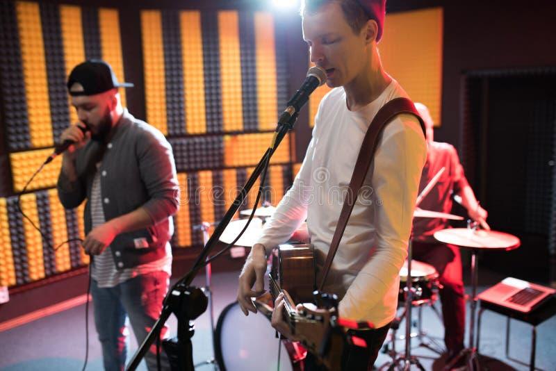 Músicos novos que cantam no estúdio do registro fotografia de stock royalty free
