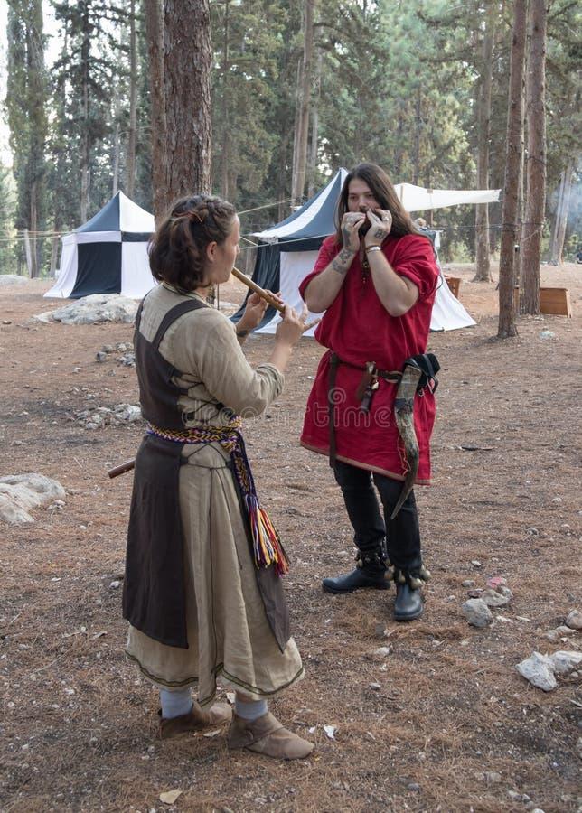 Músicos - participantes dos instrumentos musicais do jogo do ` de Viking Village do ` da reconstrução no acampamento na floresta  foto de stock royalty free