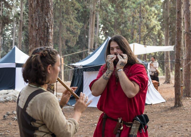 Músicos - participantes dos instrumentos musicais do jogo do ` de Viking Village do ` da reconstrução no acampamento na floresta  fotografia de stock