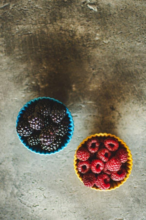 Mûres et framboises dans des cuvettes en céramique sur le fond en pierre rustique photos stock