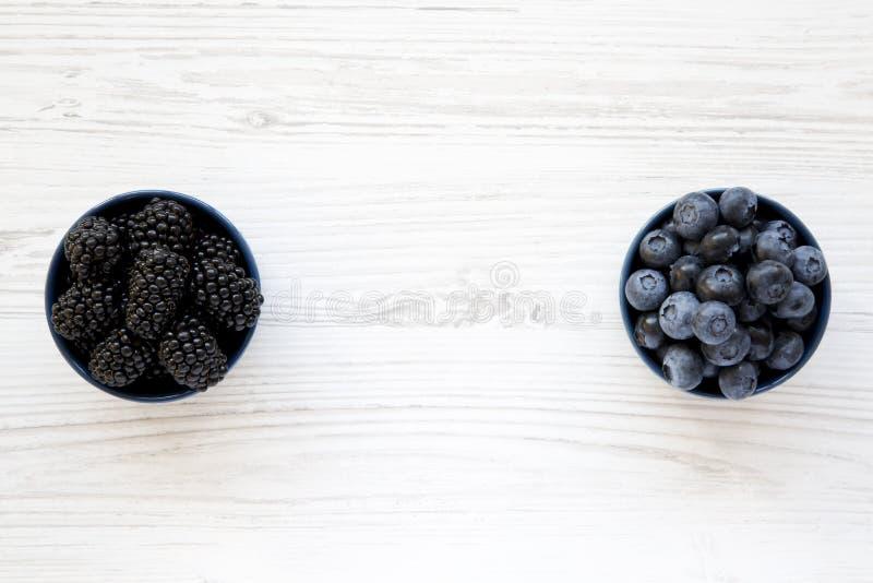 Mûres et myrtilles mûres dans des cuvettes bleues sur la table en bois blanche, vue supérieure Baie d'été D'en haut, plat, aérien image libre de droits