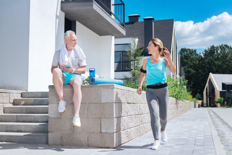 Mûrissez l'homme sportif reposant et attendant son épouse tout en prévoyant la classe de yoga images stock