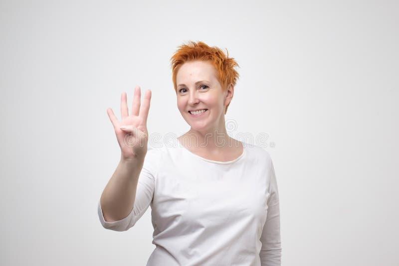 Mûrissez la femme européenne avec les cheveux rouges habillés dans le T-shirt blanc montrant quatre doigts photos stock