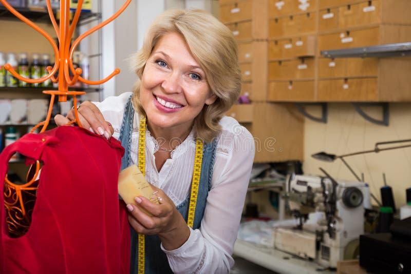 Mûrissez la robe de couture de femme blonde dans l'atelier d'habillement photo libre de droits