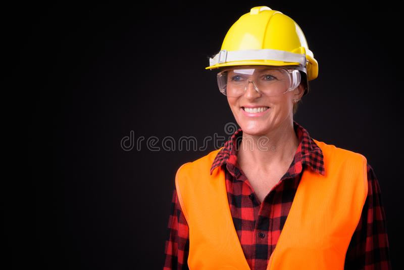 Mûrissez le beau travailleur de la construction de femme avec les cheveux courts encore photo stock
