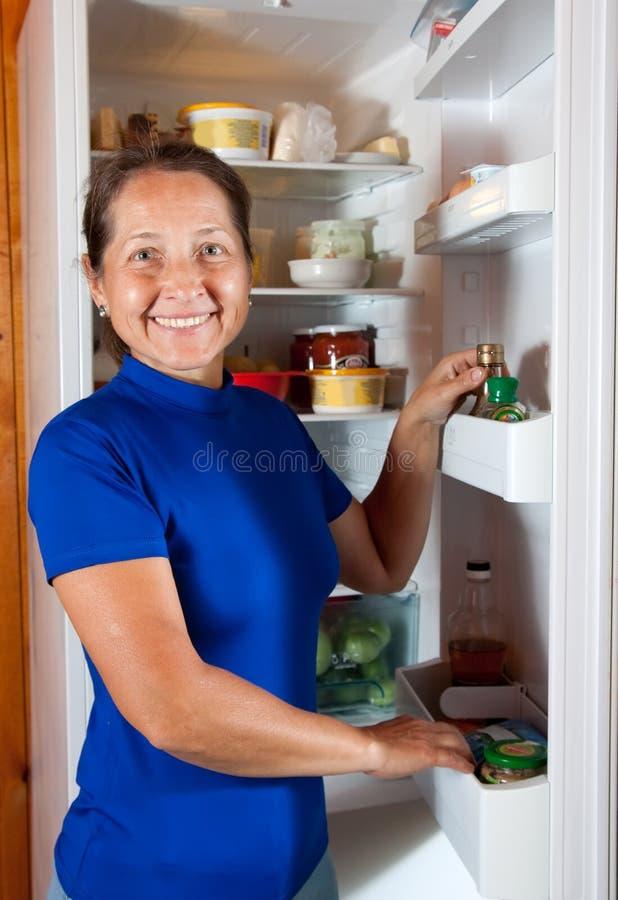 Mûrissez le femme regardant dans le réfrigérateur images stock