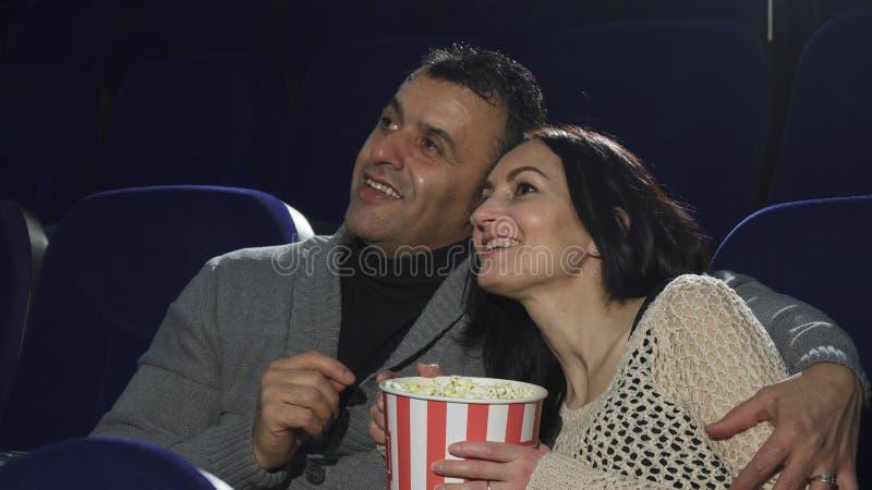 Mûrissez les couples heureux appréciant leur date au cinéma observant un film image stock