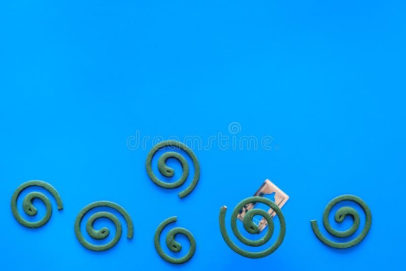 Mückenschutz für im Freien: Garten, Sommerhaus, Picknick Grüne Spirale auf blauem Draufsichtraum des Hintergrundes für Text lizenzfreie stockfotos
