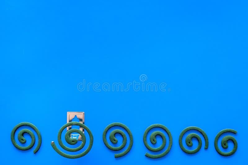 Mückenschutz für im Freien: Garten, Sommerhaus, Picknick Grüne Spirale auf blauem Draufsichtraum des Hintergrundes für Text stockfotografie