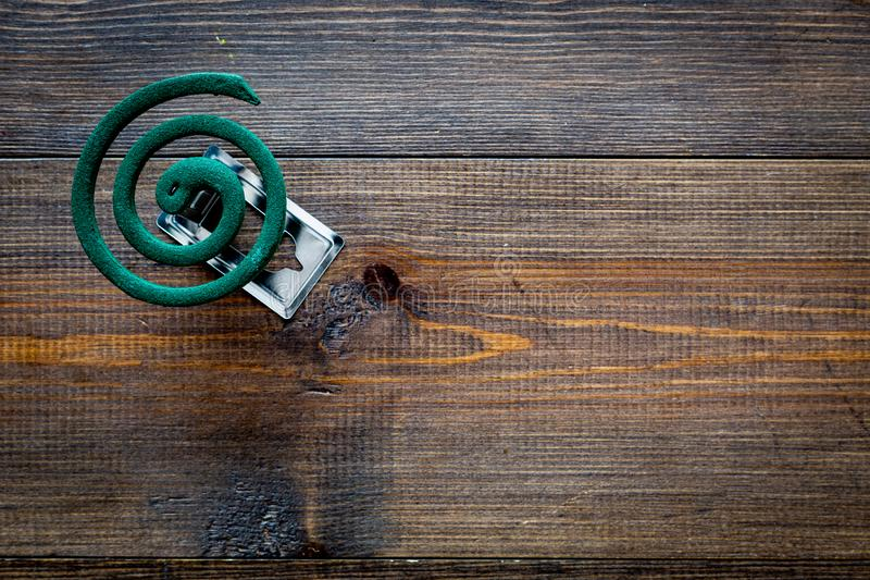 Mückenschutz für im Freien: Garten, Sommerhaus, Picknick Grüne Spirale auf dunklem hölzernem Draufsicht-Kopienraum des Hintergrun stockbild