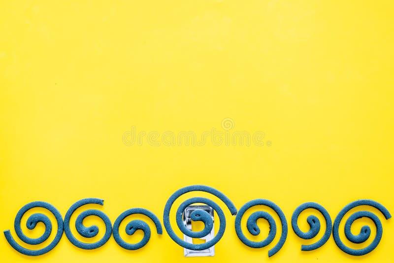 Mückenschutz für im Freien: Garten, Sommerhaus, Picknick Grüne Spirale auf gelbem Draufsicht-Kopienraum des Hintergrundes stockfotos