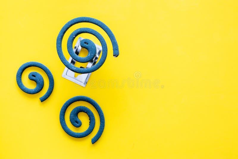 Mückenschutz für im Freien: Garten, Sommerhaus, Picknick Grüne Spirale auf gelbem Draufsicht-Kopienraum des Hintergrundes stockbild