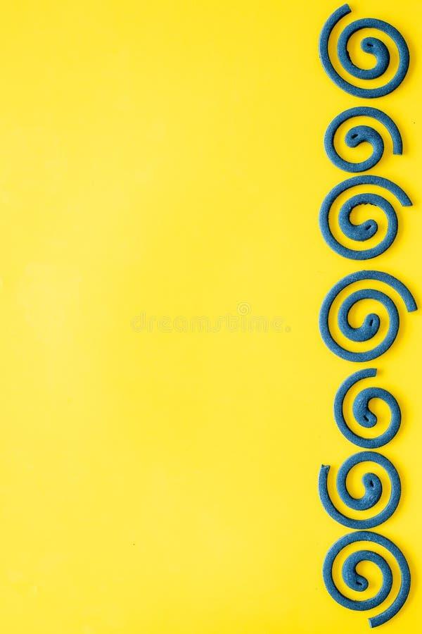 Mückenschutz für im Freien: Garten, Sommerhaus, Picknick Grüne Spirale auf gelbem Draufsicht-Kopienraum des Hintergrundes lizenzfreies stockfoto