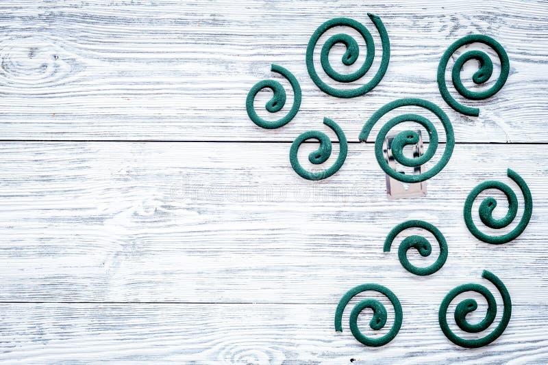 Mückenschutz für im Freien: Garten, Sommerhaus, Picknick Grüne Spirale auf grauem hölzernem Draufsicht-Kopienraum des Hintergrund stockfotografie