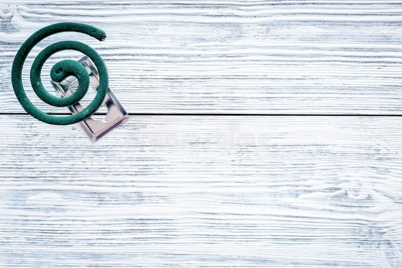 Mückenschutz für im Freien: Garten, Sommerhaus, Picknick Grüne Spirale auf grauem hölzernem Draufsicht-Kopienraum des Hintergrund stockfotos