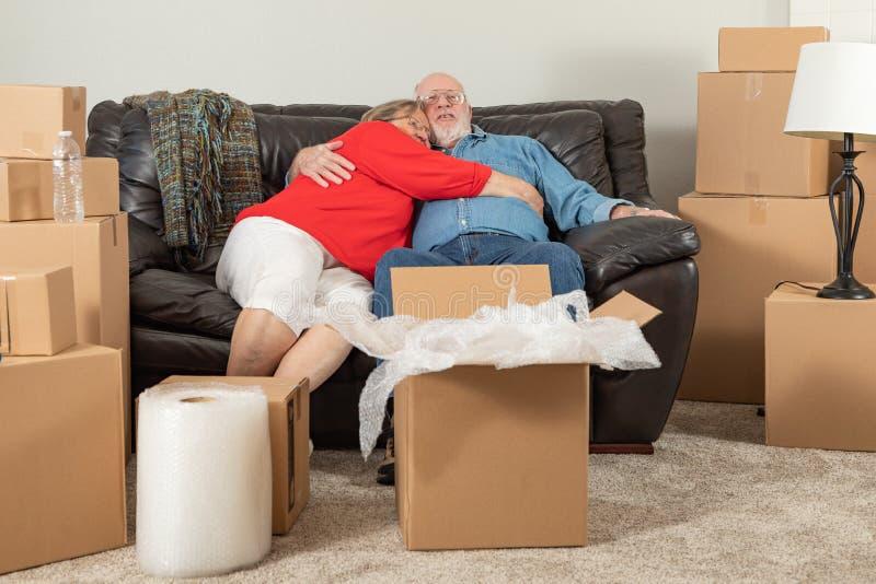 M?de ?ltere erwachsene Paare, die auf der Couch umgeben durch K?sten umarmen lizenzfreie stockfotos