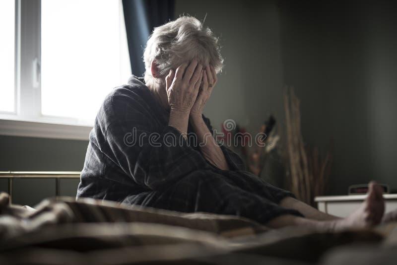 Müde ältere Frau auf ihrem Bett lizenzfreie stockbilder