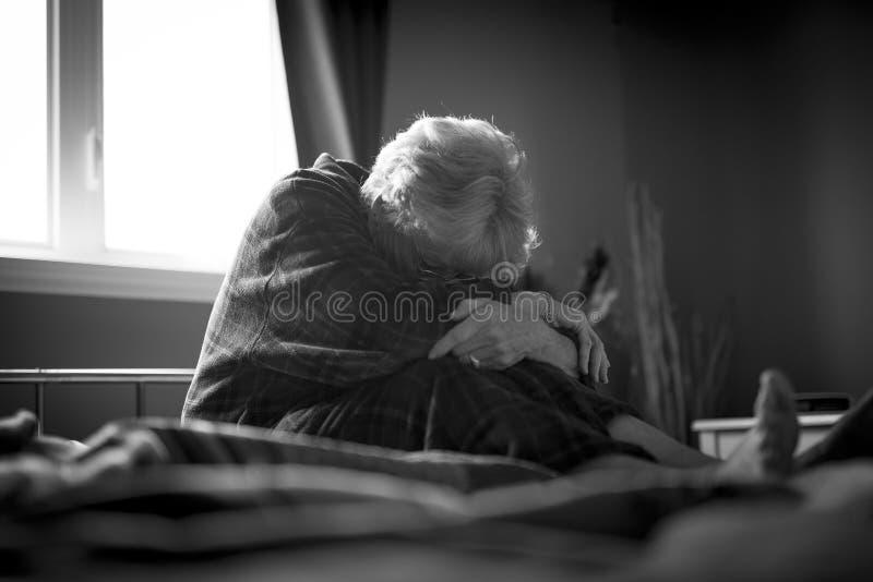 Müde ältere Frau auf ihrem Bett lizenzfreies stockbild