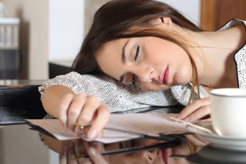 Müde überarbeitete stillstehende Frau beim Schreiben von Anmerkungen stockfotos