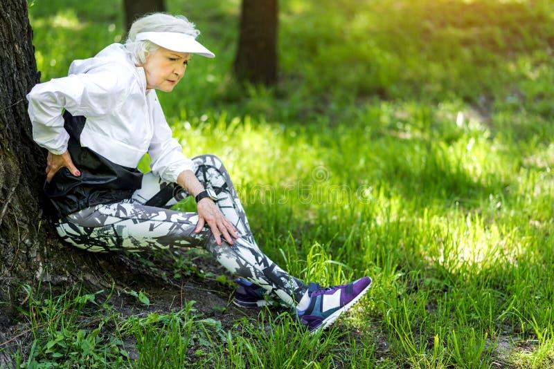 Müde alte Frau, die nach starkem draußen ausbilden stillsteht stockfotografie