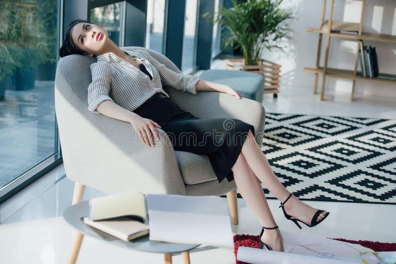 Müde asiatische Geschäftsfrau, die im Stuhl sitzt und Fenster betrachtet lizenzfreie stockbilder