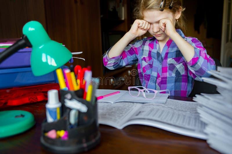 Müde Augen eines Kindes, das Hausarbeit, das Schreiben und das Lernen tut stockfotos