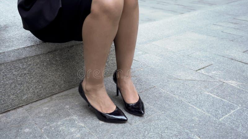 Müde Beine in den Schuhen des hohen Absatzes, Dame, die auf der Steinbank, nach der Arbeit entspannend sitzt stockbilder