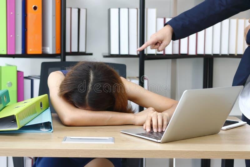 Müde betonte junge asiatische Geschäftsbiegung hinunter Kopf mit dem Chef der Hand, der an Arbeitsplatz zeigt stockfotografie