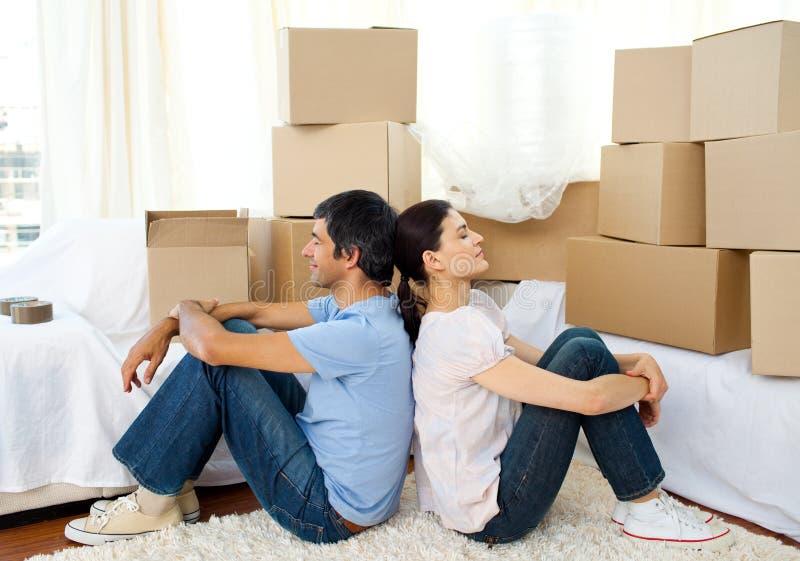 Müde entspannende Paare bei der Bewegung des Hauses stockfoto