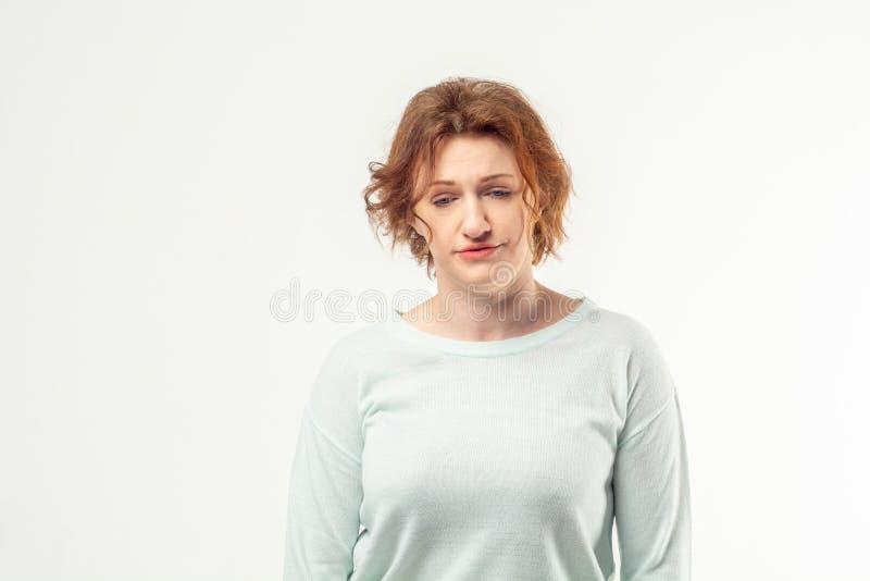 Müde erwachsene Frau, die unten schaut stockfotos