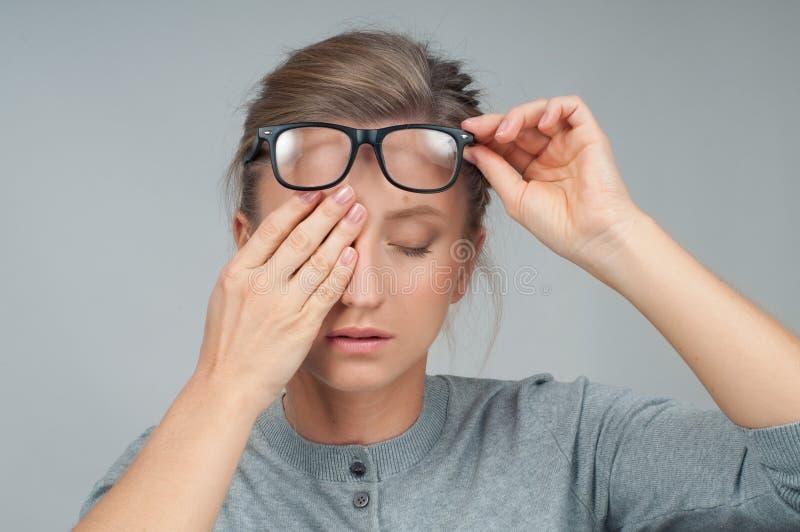 Müde Frau in den Brillen, bedeckend mustert mit den Händen stockbilder
