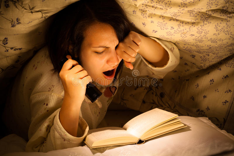 Müde Frau, die ein Buch liest stockbilder