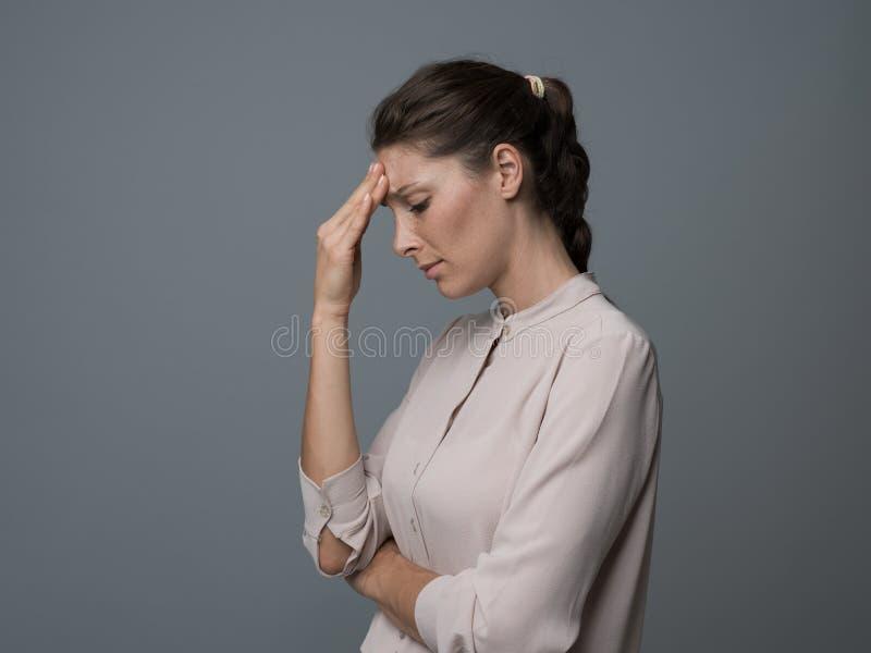Müde Frau mit Kopfschmerzen stockbild