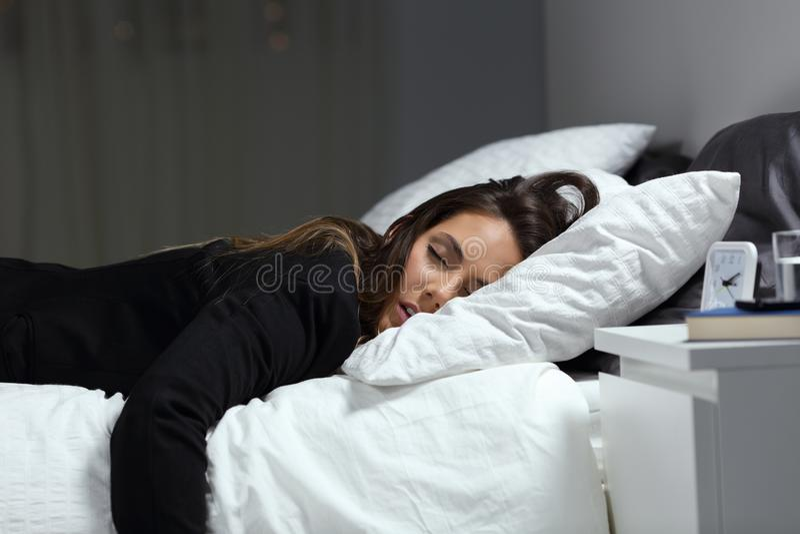 Müde Geschäftsfrau, die auf einem Bett schläft in der Nacht liegt lizenzfreie stockfotos