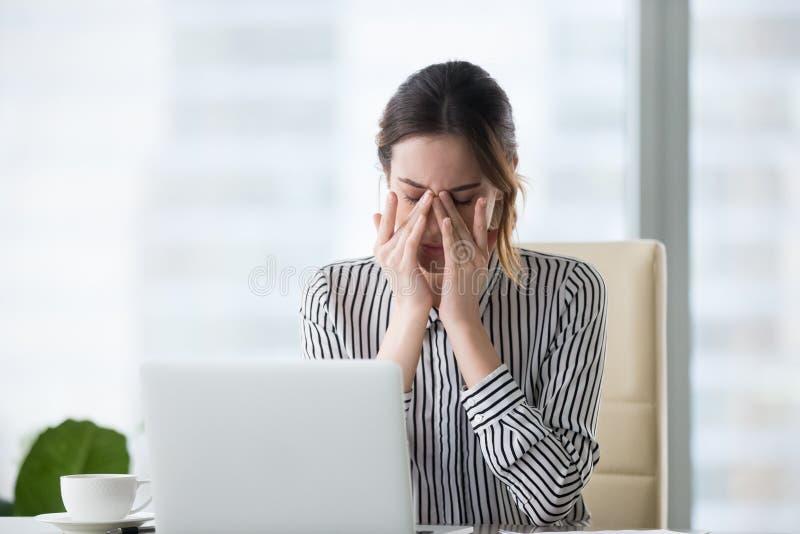 Müde Geschäftsfrau, welche die Augengefühlsbelastungs-Ermüdungskopfschmerzen entlasten die Schmerz massiert stockfotos