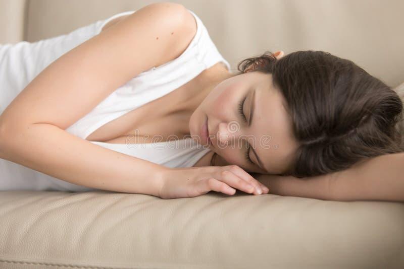 Müde junge Frau, die auf weichem Sofa schläft lizenzfreie stockfotos