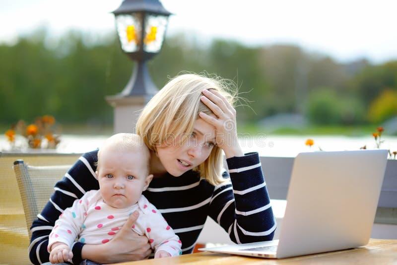 Müde junge Mutter, die oh ihren Laptop bearbeitet lizenzfreie stockfotografie