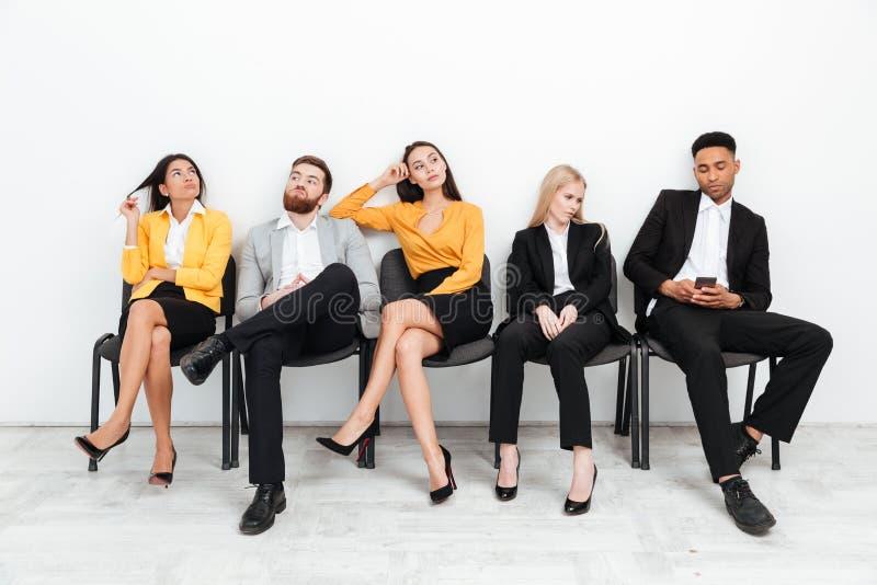 Müde Kollegen, die im Büro beim beiseite schauen sitzen stockbild