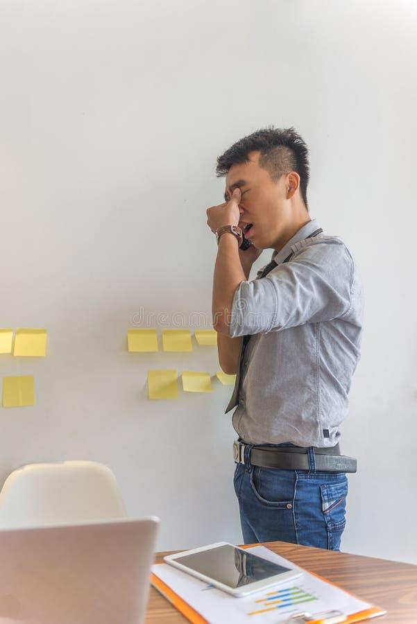 Müde Mannantwort der Telefonanruf im Büro lizenzfreie stockbilder