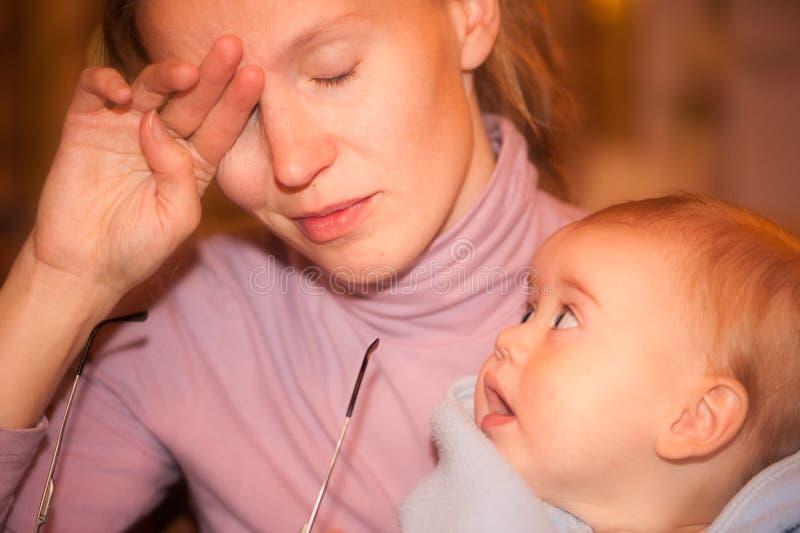 Müde Mutter mit einem neugierigen Baby in ihren Armen stockbild