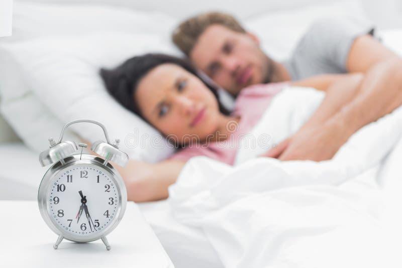 Müde Paare, die den Wecker betrachten lizenzfreie stockfotos