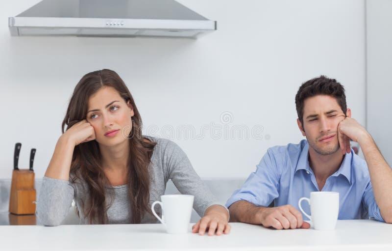Müde Paare, die am Tisch mit einem Tasse Kaffee sitzen lizenzfreie stockfotos