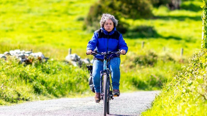 Müde reife mexikanische Frau, die ihr Fahrrad auf einem Hügel fährt lizenzfreie stockfotografie